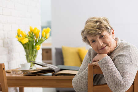 의 자 및 그녀의 뒤에 테이블에 누워 오래 된 사진 앨범에 앉아 웃는 수석 여자