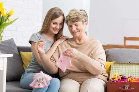 embroider: Young smiling woman sitting on a sofa and watching her grandma embroider Stock Photo