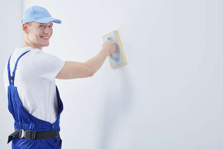 worker working: Handsome happy young man working as a interior construction worker Stock Photo