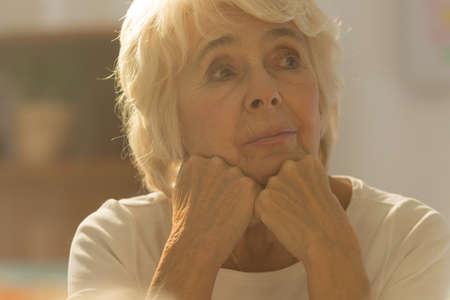 sitting pretty: Close-up of pretty worried senior woman sitting alone