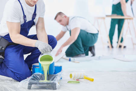 Professional interior construction worker pouring green color to paint Reklamní fotografie - 72745840