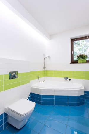 lightsome: Modern bathroom with color tiles, corner bathtub and toilet seat
