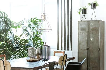 White, industriële eetkamer met metalen kast en houten tafel Stockfoto - 73008114