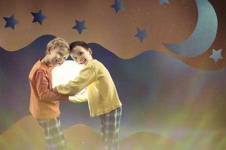 star sky: Two happy boys in pajamas on the night sky background