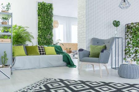 Lichte woonkamer met bank, fauteuil, pouf en groene planten