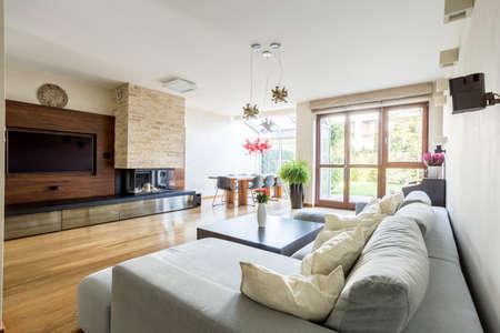 Geräumige Holz Wohnzimmer mit großen TV, Kamin und bequemen Couch Standard-Bild - 73047196