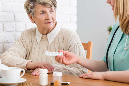 Senior woman listening to the doctor explaining her when to take medicine
