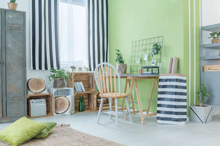 Green room with striped accessories, metal wardrobe and pallet furniture Фото со стока