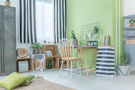 Groene kamer met gestreepte accessoires, metalen kledingkast en palletmeubilair Stockfoto