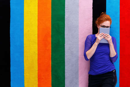 Red-haired girl covering her face by book