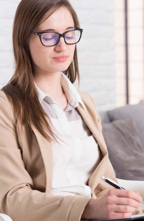 Professional young psychologist focused on taking notes Stock Photo