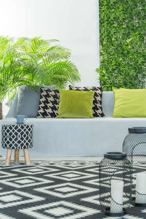Bright modern room with sofa, pattern accessories and green plants