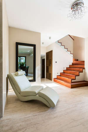 Spacious and bright corridor with place to rest and stairs to first floor Stock Photo