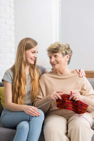 Smiling grandmother and granddaughter sitting on a sofa and smiling at each other Фото со стока