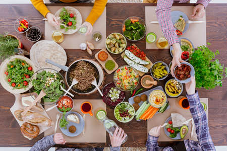 Wooden rustic table full of colorful vegetarian food