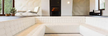 fireplace living room: Big white sofa in modern spacious living room with fireplace Stock Photo