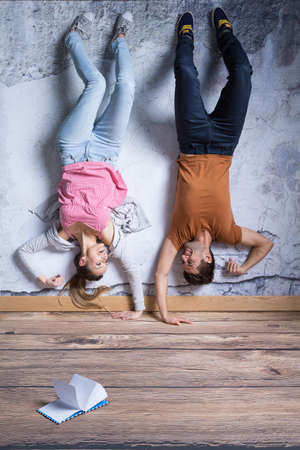 human relations: Young man and woman standing upside down