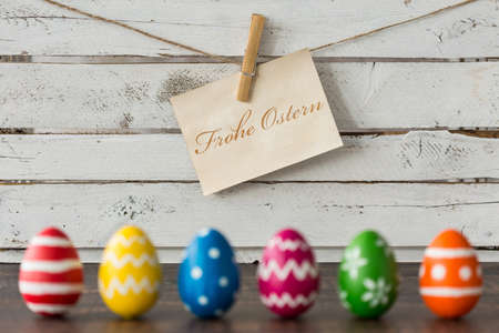 Colorful Easter eggs and paper with greetings against white plank wall