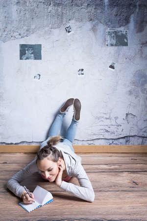 woman lying: Young woman lying on floor, writing diary