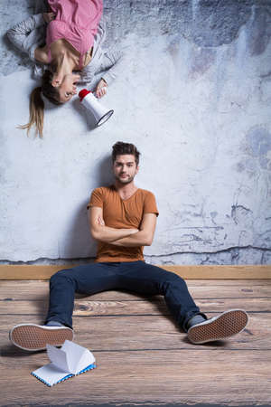 Upside down girl with megaphone and man sitting against wall