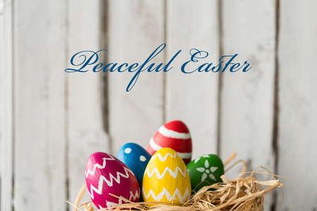 Decoração de ovos de Páscoa coloridos contra a parede de madeira