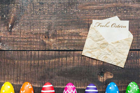 Old envelope with Easter greetings and row of Easter eggs on wooden table