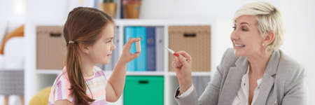 School counsellor helping little girl with learning words Stock Photo