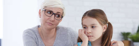 Little worried girl sitting sad at female school psychologists office