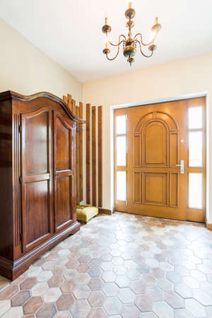 lightsome: Spacious hallway with front door and a massive wooden wardrobe