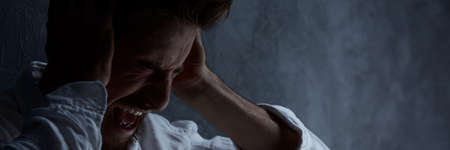 Young screaming man with mental health problems in the dark room Stock Photo
