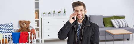 一人の男が彼の携帯電話で話していると子供の部屋