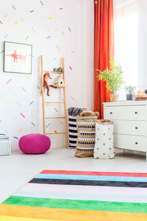 Colorful carpet and purple pouffe in modern white baby room Stock Photo