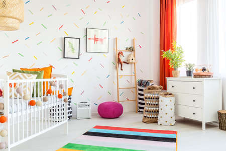 White cradle and decorations in a scandinavian baby room