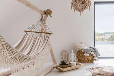 Interiér pokoje s houpací sítí a stylovými dekoracemi