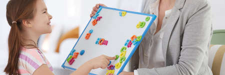 Little girl learning the alphabet through fun on classes with child therapist