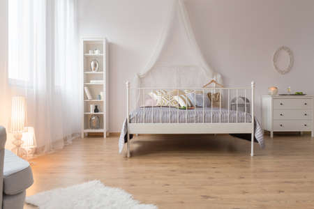bedroom furniture: Spacious bedroom with double canopy bed and white furniture