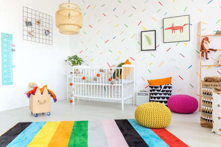 Up-to-date colorful interior of spacious baby room with cradle