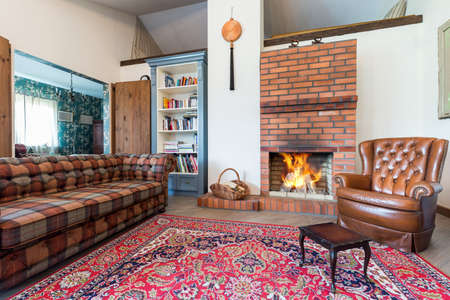 fireplace living room: Elegant rustic living room with a large carpet, sofa, leather armchair and a fireplace