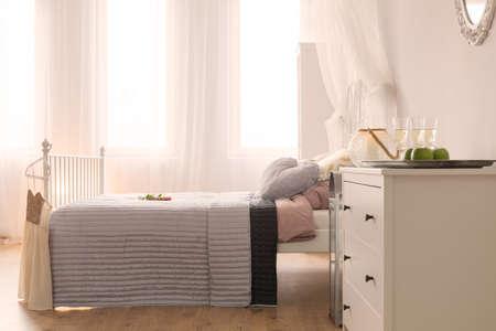 Chambre lumineuse avec lit, commode blanche et fenêtre Banque d'images