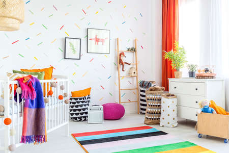 Cozy modern baby room decor with white floor and colorful additions Stock Photo