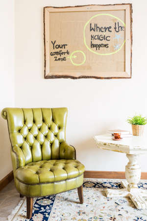lightsome: Corner in the room with the olive green leather armchair and coffee table Stock Photo