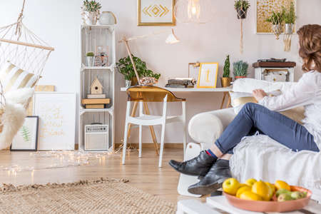 Young girl sitting on a couch in her cozy boho style room