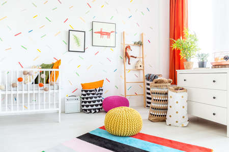 White cradle and colorful poufs in a scandinavian style baby room Stock Photo