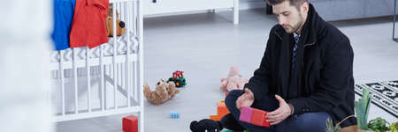 pedant: Elegant man sitting on the floor with childrens toys