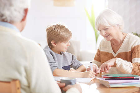Boy doing homework with grandma, sitting beside table Stock Photo