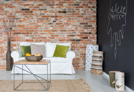 Eco living room with sofa, table, chalkboard and brick wall