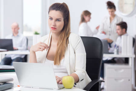 Distracted pregnant woman at work, sitting beside desk Stock Photo
