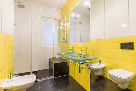 yellow walls: Modern bathroom with white and yellow walls and black floor Stock Photo