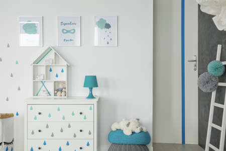 White baby bedroom with dresser, pouf and wall posters