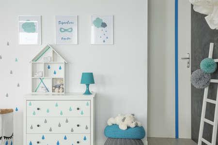 Witte babykamer met dressoir, poef en muurposters